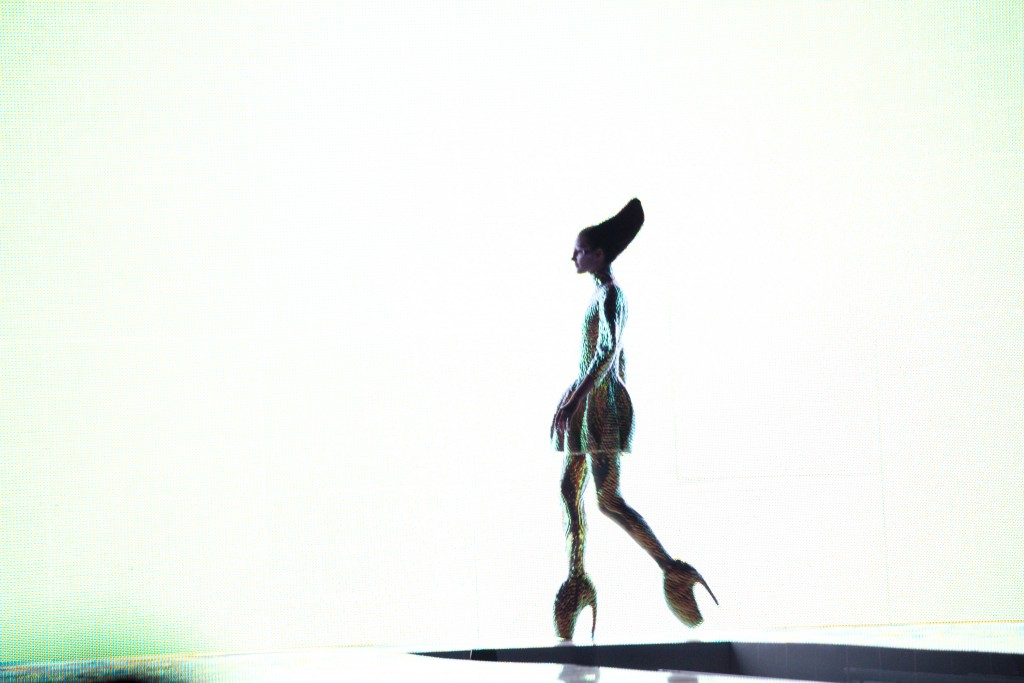 Models for Alexander McQueen's Spring 2010 show walk a runway with a video screen backdrop projecting a live feed of the show in progress as well as broadcasting on the internet. McQueen's collection was an interpretation of what people would look like if humans had evolved from sea creatures.